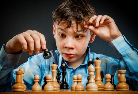 jugando ajedrez: Juego de ajedrez Wunderkind. Muchacho del empollón divertido. Foto de archivo