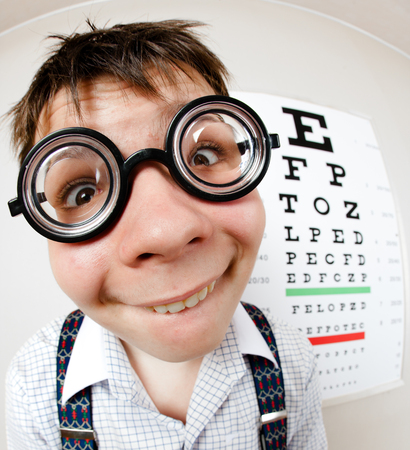 eye lens: Funny boy wearing spectacles in an office at the doctor