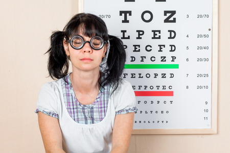 eyesight: Funny woman wearing spectacles in an office at the doctor
