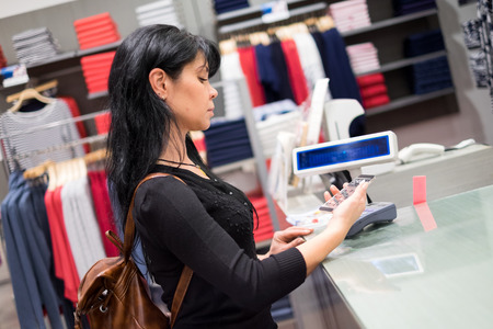 pays: Girl pays to shop using mobile phone. NFC - Near field Communication. Mobile payment. Stock Photo