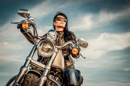 motorrad frau: Biker Mädchen in einer Lederjacke auf einem Motorrad Blick auf den Sonnenuntergang.