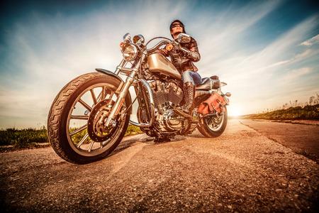 Biker ragazza in una giacca di pelle su una moto a guardare il tramonto.