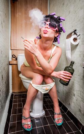 Het meisje zit in een toilet met een fles alcohol
