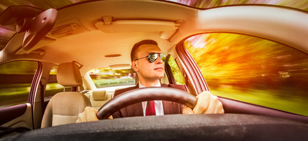 Man in a suit and sunglasses driving on a road in the car. Stock Photo