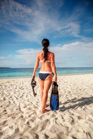 fin: Girl in bikini with snorkeling gear on the beach Maldives. Stock Photo