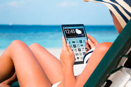 Woman on vacation lies in a sun lounger on the beach with a tablet in hands. photo