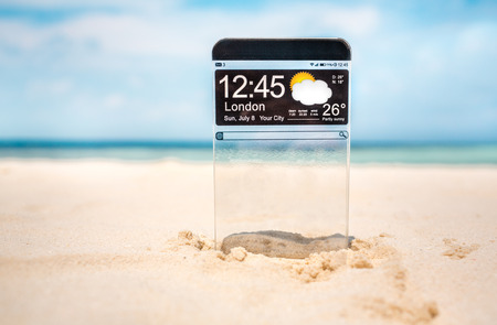 Futuristic Smart phone (copy space display) with a transparent display in the sand on the beach. Concept actual future innovative ideas and best technologies humanity. photo