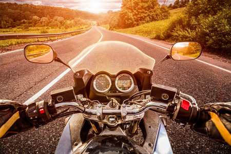 motorbikes: Biker driving a motorcycle rides along the asphalt road. First-person view.