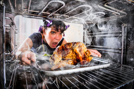 Funny Housewife overlooked roast chicken in the oven, so she had scorched (focus on chicken), view from the inside of the oven. Housewife perplexed and angry. Loser is destiny! Stock Photo