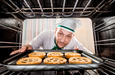 sweet bun: Chef prepares pastries in the oven, view from the inside of the oven. Cooking in the oven. Stock Photo
