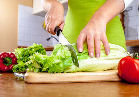 cutting vegetables: Womans hands cutting lettuce, behind fresh vegetables.