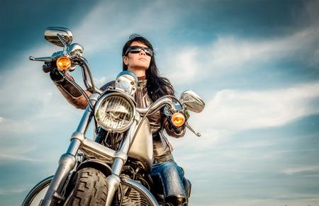 jinete: Muchacha del motorista en una chaqueta de cuero sobre una moto mirando la puesta de sol.