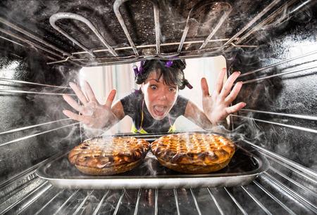 Grappige Huisvrouw hoofd gezien gebak in de oven, dus ze had verschroeid, uitzicht vanaf de binnenkant van de oven. Huisvrouw verbijsterd en boos. Loser is het lot! Stockfoto
