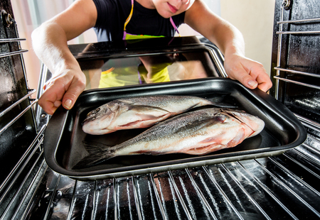 grates: Housewife prepares dorado fish in the oven, view from the inside of the oven. Cooking in the oven.