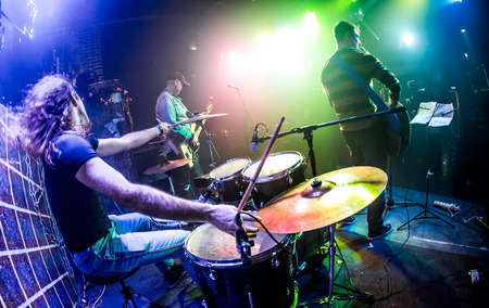 rock band: Drummer (blurred motion) playing on drum set on stage. Focus on the drum and microphone. Stock Photo