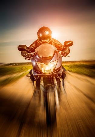 Biker in helmet and leather jacket racing on the road Standard-Bild