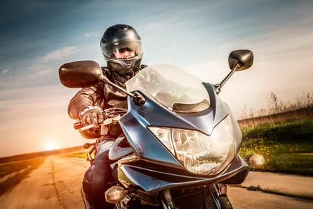 motociclista: Motorista en el casco y la chaqueta de cuero de carreras en la carretera