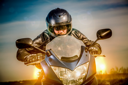 Biker in helmet and leather jacket racing on the road with the sun in the background photo
