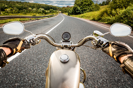 moto: Biker driving a motorcycle rides along the asphalt road. First-person view.