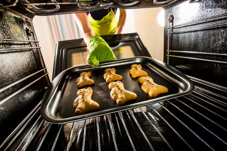wife of bath: Baking Gingerbread man in the oven, view from the inside of the oven Stock Photo
