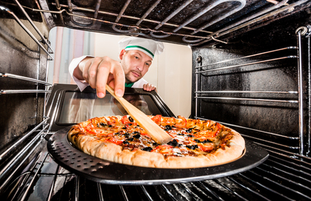 grates: Chef prepares pizza in the oven, view from the inside of the oven