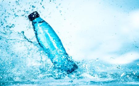 青色の背景に水のしぶきのボトル