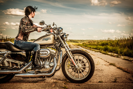 RUSSIA-JULY 7, 2013: Biker girl and bike Harley Sportster. Harley Davidson sustains a large brand community which keeps active through clubs, events, and a museum. Filter applied in post-production.
