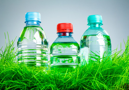 Bottle of water on the green grass photo