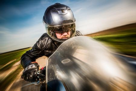 casco moto: Motorista en carreras de casco y la chaqueta de cuero en el camino Foto de archivo
