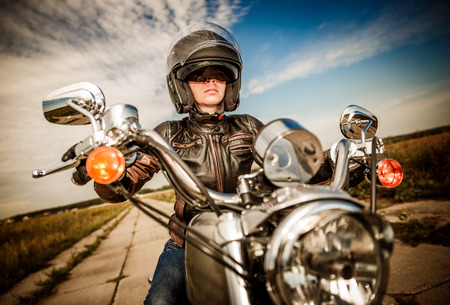 Biker girl in a leather jacket and helmet on a motorcycle photo