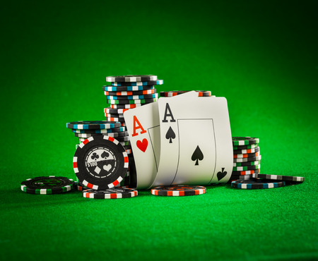 stay in the green: Stack of chips and two aces on the table on the green baize - poker game concept