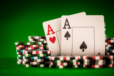 wager: Stack of chips and two aces on the table on the green baize - poker game concept