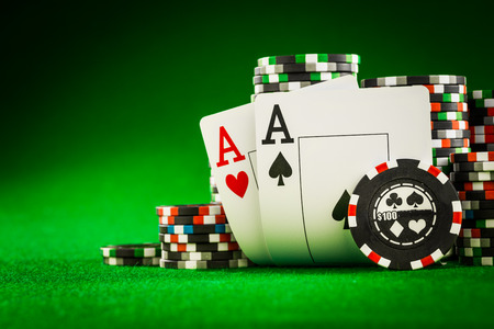 games of chance: Stack of chips and two aces on the table on the green baize - poker game concept