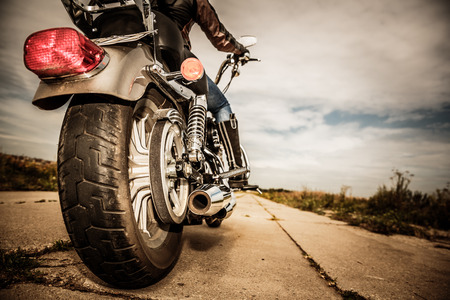 Biker girl riding on a motorcycle. Bottom view of the legs in leather boots. Focus on the rear wheel. Stock Photo