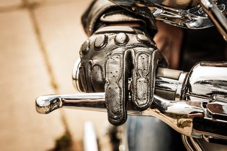Menselijke hand in een Motorcycle Racing handschoenen houdt een motorfiets gashendel. Bescherming van de handen van valpartijen en ongevallen.