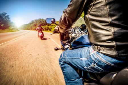 Bikers besturen van een motorfiets rijdt langs de asfaltweg (vage motie). First-person view. Focus op het dashboard van een motorfiets