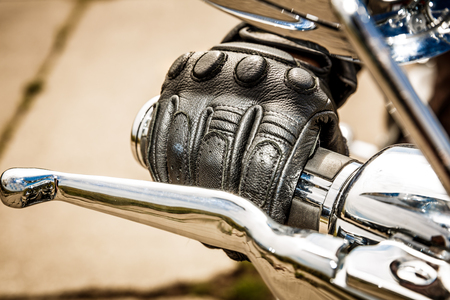 Human hand in a Motorcycle Racing Gloves holds a motorcycle throttle control. Hand protection from falls and accidents. photo
