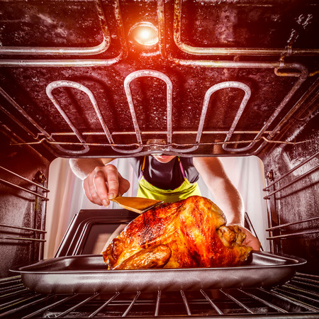 Housewife prepares roast chicken in the oven, view from the inside of the oven. Cooking in the oven. photo