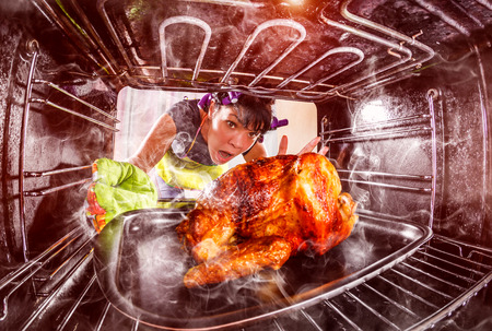 Funny Housewife overlooked roast chicken in the oven, so she had scorched , view from the inside of the oven. Housewife perplexed and angry. Loser is destiny! Stock Photo