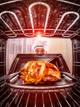 oven chicken: Chef prepares roast chicken in the oven, view from the inside of the oven. Cooking in the oven. Stock Photo