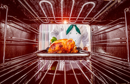 Chef prepares roast chicken in the oven, view from the inside of the oven. Cooking in the oven. photo