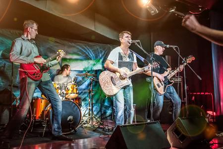 Band presteert op het podium, rock muziek concert. Waarschuwing - authentieke opnamen met hoge ISO in moeilijke lichtomstandigheden. Een beetje graan en vage motie effecten.