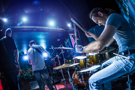 Drummer playing on drum set on stage. Warning - Focus on the drum, authentic shooting with high iso in challenging lighting conditions. A little bit grain and blurred motion effects.