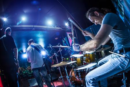 Drummer spelen op drumstel op het podium. Waarschuwing - Focus op de trommel, authentieke opnamen met hoge ISO in moeilijke lichtomstandigheden. Een beetje graan en vage motie effecten. Stockfoto - 33679694