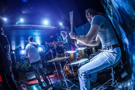 Drummer spelen op drumstel op het podium. Waarschuwing - Focus op de trommel, authentieke opnamen met hoge ISO in moeilijke lichtomstandigheden. Een beetje graan en vage motie effecten.