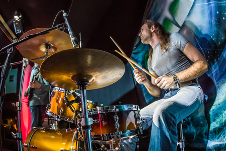 Drummer (focus on the drum and microphone) playing on drum set on stage.