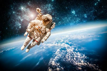 惑星の地球を背景に宇宙の宇宙飛行士。このイメージの NASA によって供給の要素。
