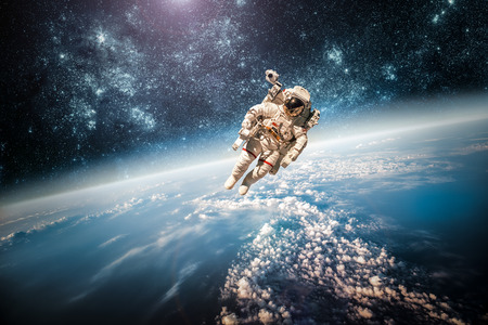 Astronaut in outer space against the backdrop of the planet earth. Elements of this image furnished by NASA. Stock Photo