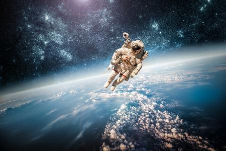 Astronauta w przestrzeni kosmicznej na tle planety Ziemia. Elementy tego zdjęcia dostarczone przez NASA.