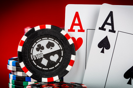 gambling chip: Stack of chips and two aces on the table on the red baize - poker game concept